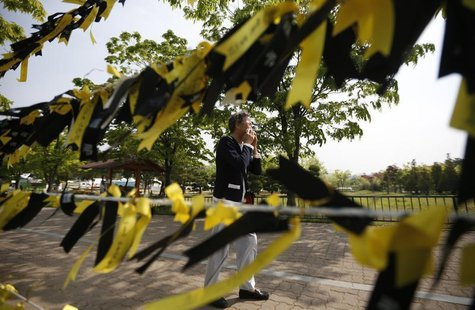 A mourner cries next to yellow ribbons dedicated to missing and dead passengers of sunken passenger ship Sewol, after paying tribute at the