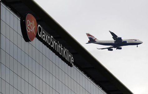 A British Airways airplane flies past a signage for pharmaceutical giant GlaxoSmithKline (GSK) in London April 22, 2014. REUTERS/Luke MacGre