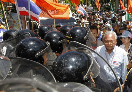Anti-government protest leader Suthep Thaugsuban walks past Air Force military personnel during a rally at the Air Force base in Bangkok May