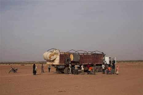 Nigeriens, who are travelling north in the direction of Libya, board a truck in Agadez March 17, 2014. Picture taken March 17, 2014. REUTERS