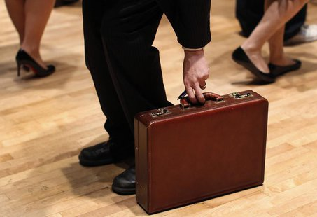 A man grabs his briefcase as he waits in line to speak with employers at the UJA-Federation Connect to Care job fair in New York, March 21,