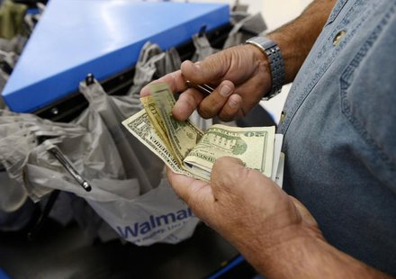 A customer counts his cash at the checkout lane of a Walmart store in the Porter Ranch section of Los Angeles November 26, 2013. REUTERS/Kev