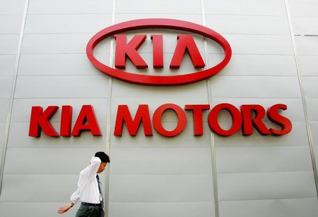 A South Korean man walks past the logo of Kia Motors at its headquarters in Seoul August 29, 2005.