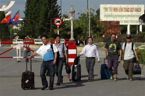 Chinese nationals cross to Cambodia from Vietnam at the Bavet international checkpoint in Svay Rieng province May 15, 2014. REUTERS/Samrang