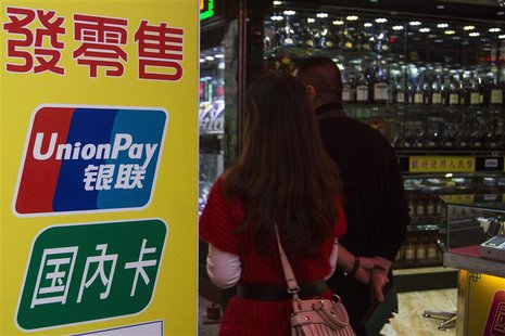 Chinese visitors walk past a sign for China UnionPay outside a pawnshop in Macau, in this November 20, 2013 file photo. REUTERS/Tyrone Siu/F