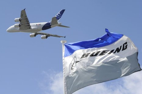 Boeing flags flutter as an Airbus A380, the world's largest jetliner, takes part in a flying display during the 49th Paris Air Show at the L