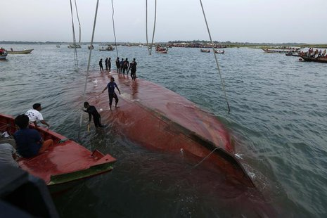 Rescue workers stand on the partially salvaged M.V. Miraj-4 ferry after it capsized on the Meghna river at Rasulpur in Munshiganj district M