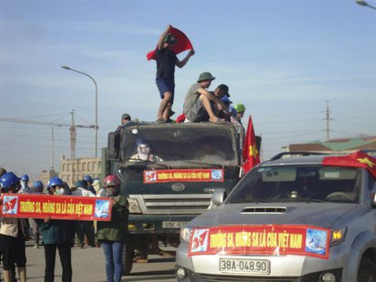 "Protesters display banners which read, ""Paracels and Spratlys belong to Vietnam"", outside the construction site of a Formosa steel mill in H"