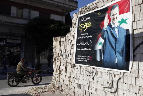 A man on a motorcycle rides past a poster depicting Syria's President Bashar al-Assad on a wall in the pro-government al-Zahraa neighbourhoo