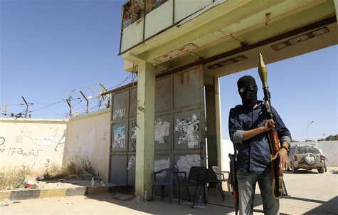 A militia stands guard in front of the entrance to the February 17 militia camp after Libyan irregular forces clashed with them in the easte