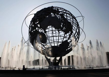 A woman is seen in silhouetted against the sun at the Unisphere fountain at Flushing Meadows-Corona Park in the Queens borough of New York J