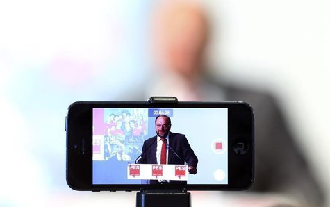 A journalist records the speech of Socialist candidate for European Commission president, Martin Schulz, with his mobile phone during a news