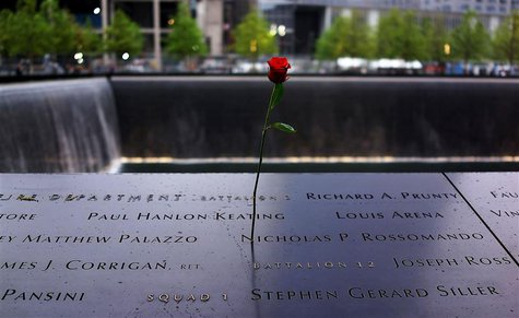 A rose is placed on a name engraved along the South reflecting pool at the Ground Zero memorial site during the dedication ceremony of the N
