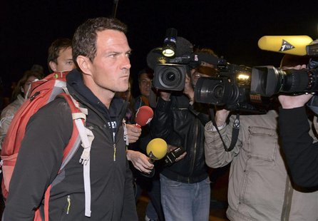 Journalists surround convicted rogue trader Jerome Kerviel (L) as he arrives on the Franco-Italian border in Menton, May 18, 2014. REUTERS/J