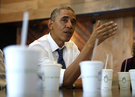 U.S. President Barack Obama talks while having lunch with construction workers at Shake Shack in Washington May 16, 2014. REUTERS/Kevin Lama