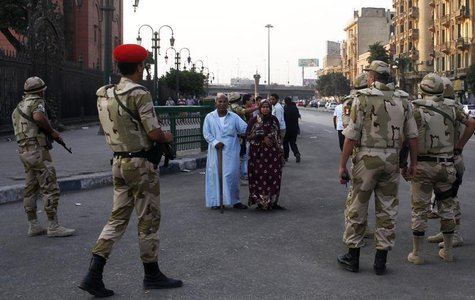 Pedestrians look as the Egyptian army soldiers divert traffic away from the front of the Egyptian museum in Cairo, July 9, 2013. REUTERS/Asm