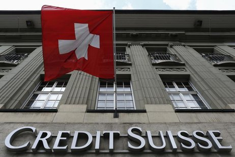 The logo of Swiss bank Credit Suisse is seen below the Swiss flag at a building in the Federal Square in Bern May 15, 2014. REUTERS/Ruben Sp