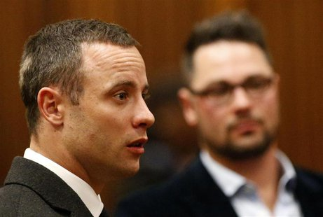 Olympic and Paralympic track star Oscar Pistorius (L) looks on next to his brother Carl at the end of his trial, at the North Gauteng High C