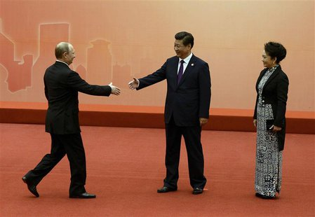 Russian President Vladimir Putin (L) is greeted by the Chinese President Xi Jinping (C) and his wife Peng Liyuan before the group photo even