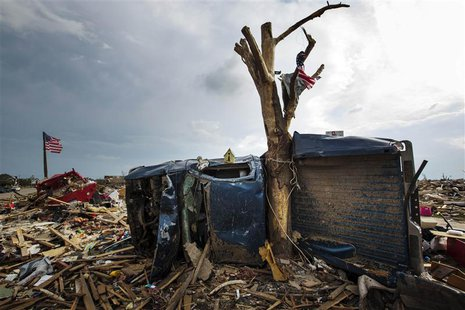 A wreckage of a pickup truck is wrapped around a tree trunk after being thrown there by by a tornado in Moore, Oklahoma in this May 25, 2013