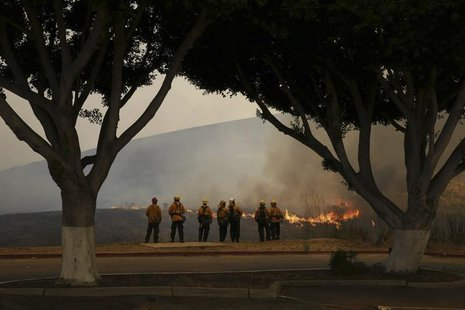 Firefighters watch the Las Pulgas Fire at Camp Pendleton, California in this May 16, 2014 handout photo from the USMC. REUTERS/Cpl. Sarah Wo