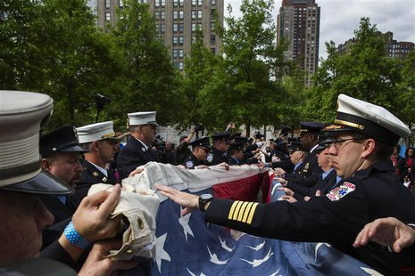 Members of an honor guard fold the National 9/11 Flag, donated by New York Says Thank You Foundation, on the grounds of the 9/11 Memorial Pl
