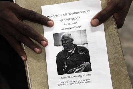 A person holds a flyer announcing a memorial service for U.S. missionary George Knoop, an elder with the Quisqueya Chapel, during the servic