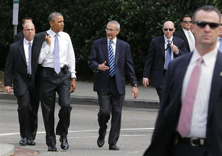 U.S. President Barack Obama (2nd L) walks with White House counselor John Podesta (C) as they were surrounded by agents of the U.S. Secret S
