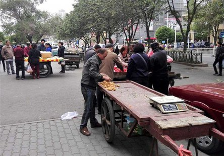 Vendors undersell fruits at an open market near the site of a blast in Urumqi, Xinjiang Uyghur Autonomous Region May 22, 2014. REUTERS/CNSph