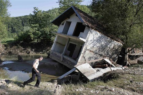 A man walks past a house tilted by floods in the town of Valjevo, southwest from Belgrade May 21, 2014. Picture taken May 21. REUTERS/Marko
