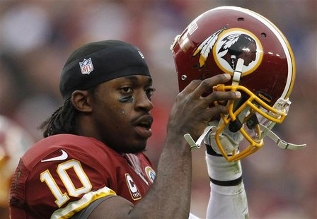 Washington Redskins quarterback Robert Griffin III puts his helmet back on after being tackled by the Baltimore Ravens defense in the first