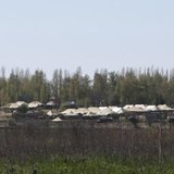 Russian military vehicles and army tents are seen in a field outside the village of Severny in Belgorod region near the Russian-Ukrainian bo