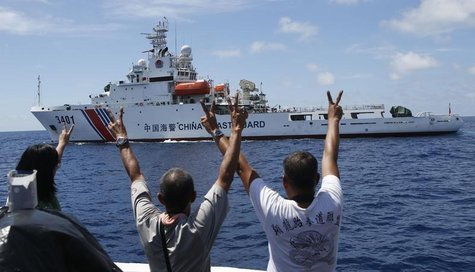Philippine Marines and a local television reporter (L) gesture towards a Chinese Coast Guard vessel, which twice attempted to block a Philip