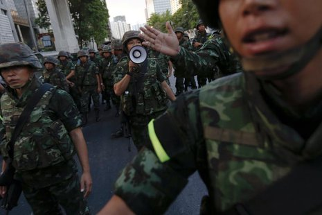 Soldiers try to control a crowd protesting against military rule in central Bangkok, a day after the Thai army chief seized power in a coup