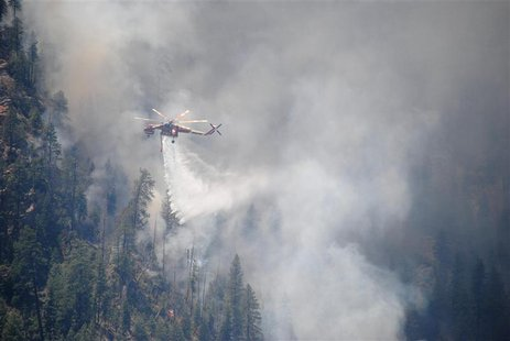 A water-dropping helicopter makes its delivery at the Slide Fire in Oak Tree Canyon near Sedona, Arizona in this May 22, 2014 handout photo