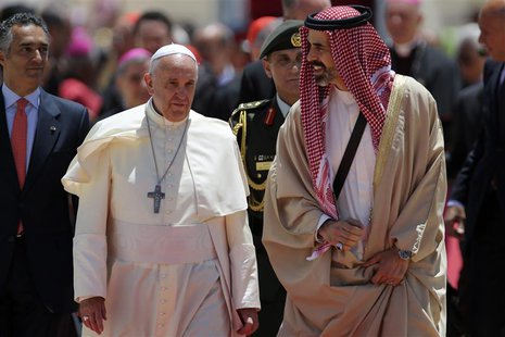 Pope Francis (2nd L) is welcomed by Jordan's Prince Ghazi bin Muhammad (R) upon his arrival at Queen Alia International airport in Amman May