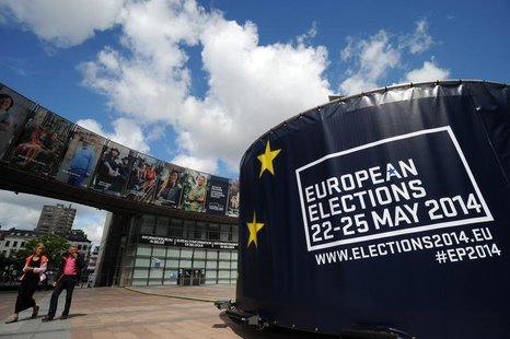 People walk in front of visuals promoting the European elections in front of the European Parliament in Brussels May 24, 2014. REUTERS/Eric