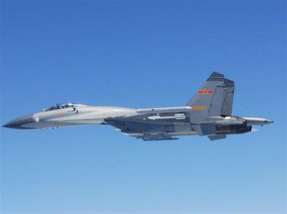 A Chinese SU-27 fighter flies over the East China Sea, in this handout photo taken May 24, 2014 and released by the Defense Ministry of Japa