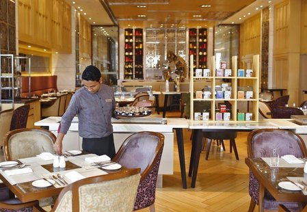 An employee sets a table inside a restaurant at the Crown Plaza hotel, run by the InterContinental Hotels Group (IHG), in New Delhi January