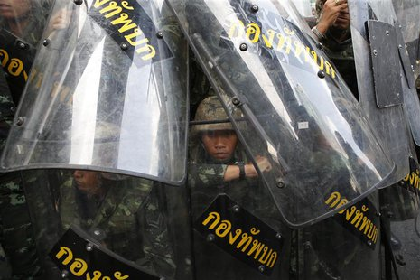 A soldier looks out from behind shields as they take up position to block protestors at a shopping district in central Bangkok May 25, 2014.