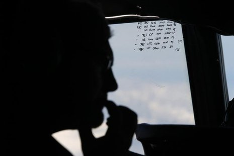 A crew member aboard a Royal New Zealand Air Force P-3K2 Orion aircraft is pictured alongside handwritten notes of other search craft in the