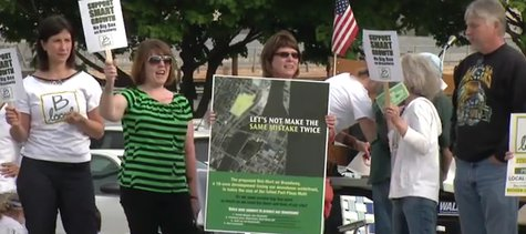 Protesters gather outside Walmart's neighborhood meeting at Neville Public Museum on May 27, 2014. (Photo from: FOX 11/YouTube).