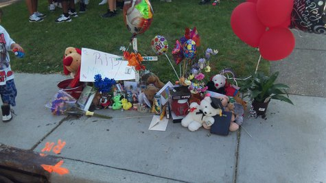 Orange Paint on the curb marks the location the youngster fell, and where a temporary memorial has been placed.