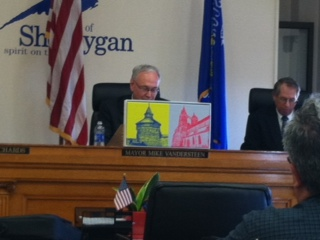 Mayor Vandersteen shows off gift of artwork from Esslingen.