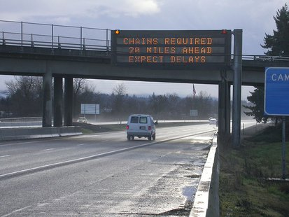 A variable message signs warns drivers that chains are required ahead. (Photo By Oregon Department of Transportation (Message sign  Uploaded by AlbertHerring) [CC-BY-2.0 (http://creativecommons.org/licenses/by/2.0)], via Wikimedia Commons)