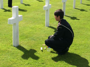 A member of the band visits the grave of a soldier from Michigan.