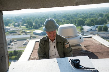 John Castrale, nongame bird biologist for Indiana Department of Natural Resources Division of Fish and Wildlife, cleans out the peregrine falcon nest box on the rooftop of Indiana State University's now vacant Statesman Towers on May 28.