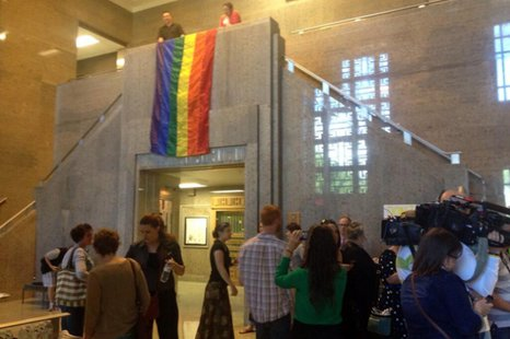 A rainbow flag is unfurled at the Outagamie County Administration Building June 9, 2014, as same-sex couples are allowed to begin filing paperwork for marriages. (Photo from: FOX 11).