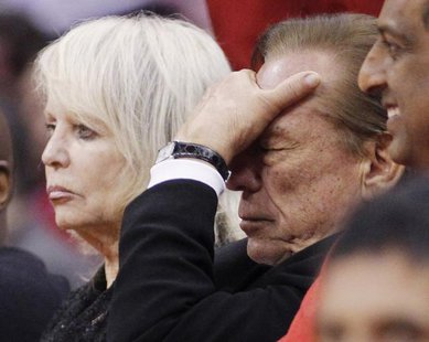 Los Angeles Clippers owner Donald Sterling (R) puts his hand over his face as he sits courtside with his wife Shelly (L) while the Clippers trail the Chicago Bulls in the second half of their NBA basketball game in Los Angeles in this December 30, 2011 file photo. CREDIT: REUTERS/DANNY MOLOSHOK/FILES