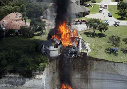 Smoke rises from a house deliberately set on fire, days after part of the ground it was resting on collapsed into Lake Whitney, Texas June 13, 2014. Credit: Reuters/Brandon Wade